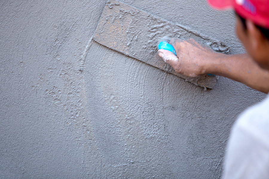 man working a cement wall